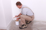 Painter painting baseboards