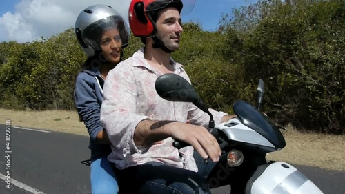 Young people riding motorbike on vacation