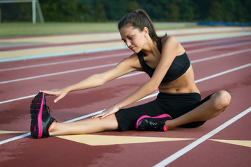 Fitness Woman Stretching on a Track with Blurred Background