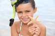 Little girl at the beach holding star fish