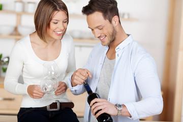 lachendes paar mit einer flasche wein