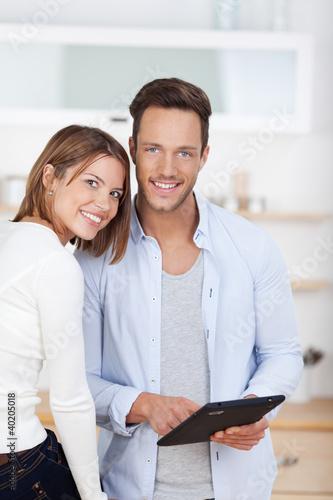 junges paar mit tablet-computer in der küche