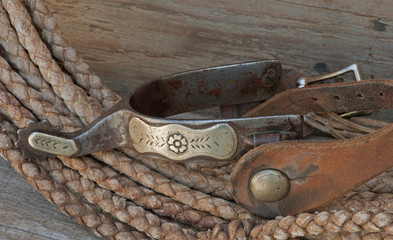 Closeup engraved antique spur on rope background