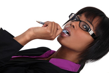 Woman chewing pen whilst thinking