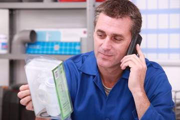 Plumbers merchant on the phone with a part in hand