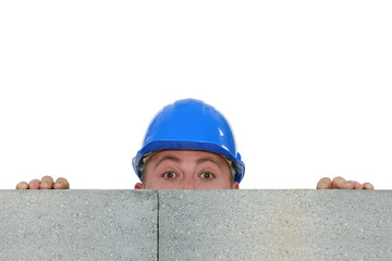 Construction worker hiding behind a wall