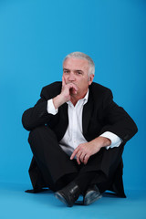 middle-aged man in black suit sitting on the floor