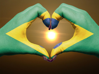 Heart and love gesture by hands colored in brazil flag during be