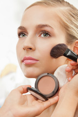 Makeup artist apply blush on cheeks