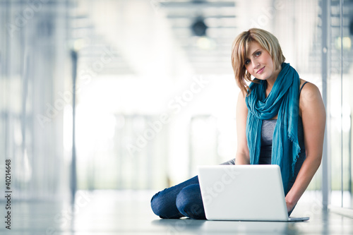 Pretty young female student with a laptop computer on college/un