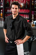 Professional barman in black standing bar