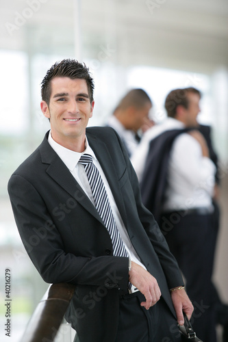 Smiling banker standing in a hall