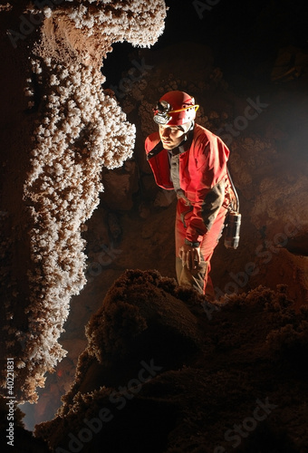 Beautiful stalactites in a cave with a speleologist
