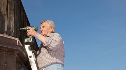 Mann auf Leiter mit Bohrmaschine