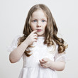 Portrait of a beautiful little girl in a white dress