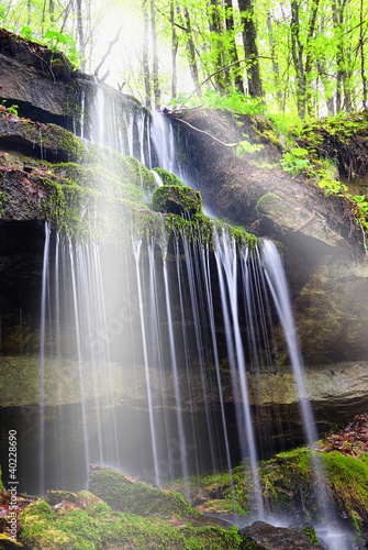 sunbeam over the waterfall in the forest
