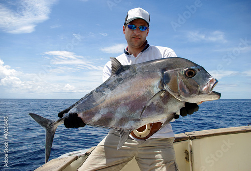 Happy  fisherman holding a trevally jack
