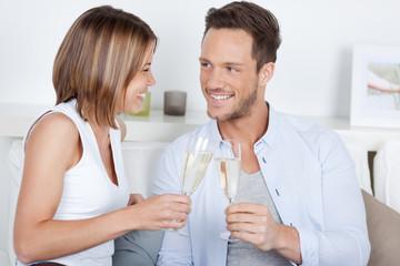 glückliches junge paar stößt mit sekt an