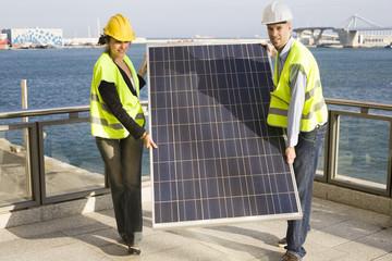Engineers carry solar panel