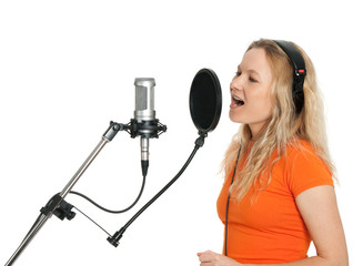 Girl in orange t-shirt singing with studio microphone