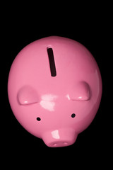 Top view of a pink piggy bank isolated on black