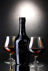Glasses of brandy and bottle on gray background