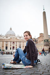 Pretty young female tourist studying a map at St. Peter's square