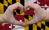 over american state flag of maryland showed heart and love gestu
