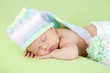 adorable baby weared cap sleeping on stomach