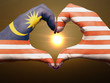 Heart and love gesture by hands colored in malaysia flag during