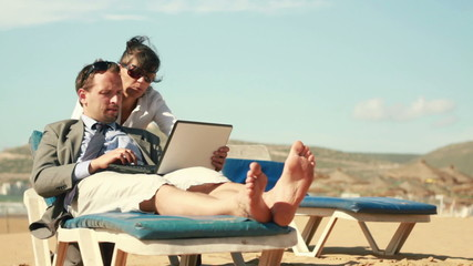 Business people working on laptop and relaxing on the beach