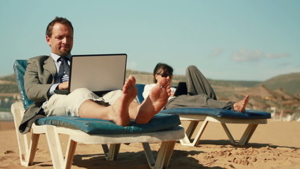 Business people working on laptop and tablet on the beach
