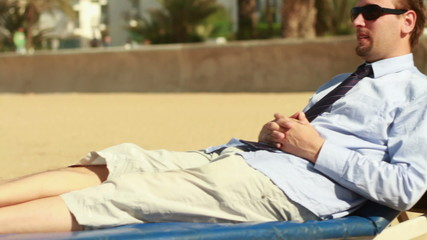 Businessman relaxing on sunbed on the beach, steadicam shot