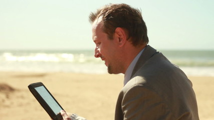 Businessman working on tablet computer on beach by the sea