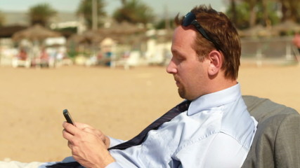 Businessman with smartphone on the beach, steadicam shot