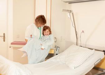 Krankenschwester trägt Kind zum Bett