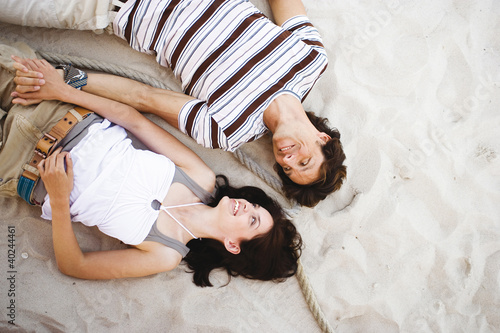 Young couple lying on sand, smiling, overhead view