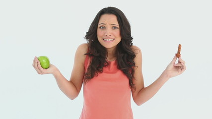 A indecisive woman tries to choose between an apple and a cookie