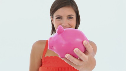 Girl saving cash in her piggy-bank