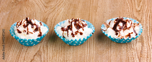 Creamy cupcakes on wooden background