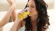 Brunette haired woman drinking orange juice