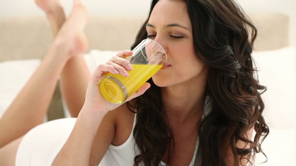 Brunette haired woman drinking orange juice