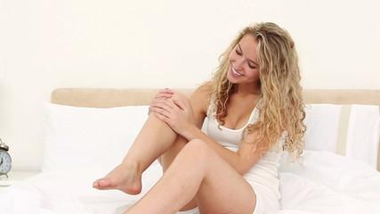 Blonde applying moisturiser cream