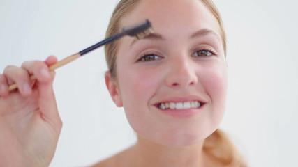 Smiling blonde woman brushing her eyebrows