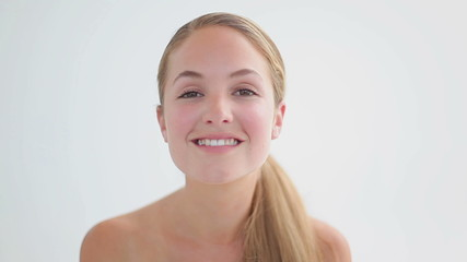 Smiling woman using a cotton wool on her face