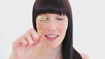 Smiling brunette using an eyelash curler