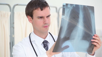 Serious surgeon looking at a chest x-ray