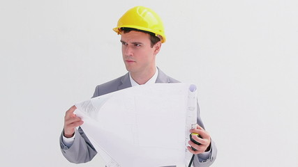 Serious worker reading blueprints