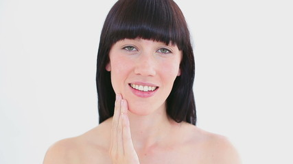 Smiling woman massaging her cheek