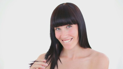 Smiling woman holding a strand of her hair